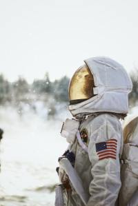 person in space suit looking at the sky